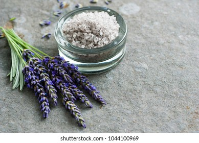 bath salt and fresh lavender flowers on basalt stone background