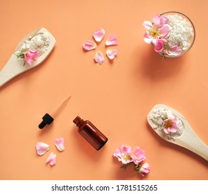 Bath salt in wooden spoons and a glass jar with flowers and rose petals, on a natural beige background. The view from the top.