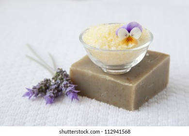 Bath salts and organic soap over white towel background