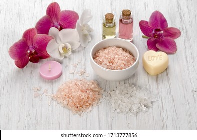 Bath salts, pink Orchid flower, candle and soap on white wooden background as Spa concept body care at home or salon