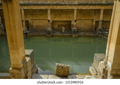 BATH, SOMERSET, UK - SEPTEMBER 15, 2019: Roman Baths at Bath Spa, Somerset. A tour guide dressed as a Roman stands by the Great Bath, the main bathing pool, it is a UNESCO World Heritage Site.