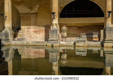 BATH, SOMERSET, UK - SEPTEMBER 15, 2019: Roman Baths at Bath Spa, Somerset. A tour guide dressed as a Roman stands by the Great Bath, the main bathing pool. It is a UNESCO World Heritage Site.