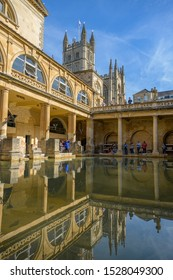 BATH, SOMERSET, UK - SEPTEMBER 15, 2019: Roman Baths at Bath Spa, Somerset. The Great Bath and view towards Bath Abbey and reflections in the pool. It is a UNESCO World Heritage Site.