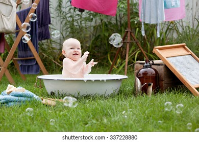 Bath time!  Adorable baby girl playing in a vintage wash basin.  Other vintage clothes washing items scattered around with laundry hanging from a drying rack in the background.