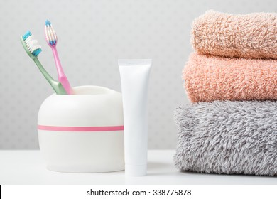 Bath towels of different colors, thoot brushes and toothpaste on light background