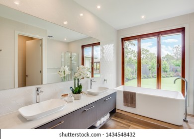 Bath tub adjacent to a dual sink counter, with windows facing the lawn.