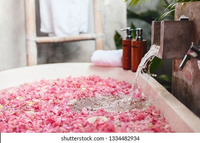 Bath tub with flower petals filling with water. Organic spa relaxation in luxury Bali outdoor bathroom.