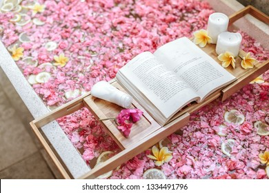 Bath tub with flower petals and lemon slices. Book, candles and beauty product on a tray. Organic spa relaxation in luxury Bali outdoor bathroom.