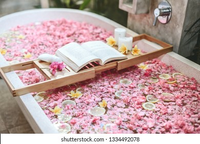 Bath tub with flower petals and lemon slices. Book and candles on a tray. Organic spa relaxation in luxury Bali outdoor bathroom.