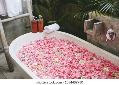 Bath tub with flower petals, towel and beauty products. Organic spa relaxation in luxury Bali outdoor bathroom.