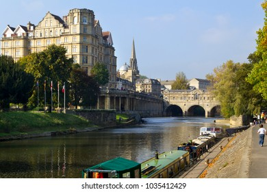 Bath, UK - 10th October 2010: Visitors sightseeing on the banks of the River Avon in Autumn sunshine in the City of Bath, Somerset, UK. Bath is a UNESCO World Heritage Site famous for architecture