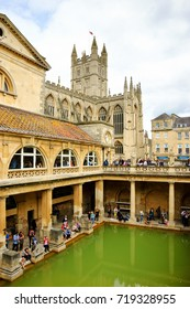 BATH, UK  - AUGUST 24, 2017: Tourists visiting inside Roman Baths complex and cathedral building at background. City of Bath  is a UNESCO World Heritage Site.