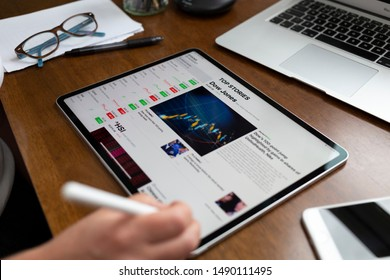 BATH, UK - AUGUST 28, 2019 : Person using an Apple iPad Pro on a desk displaying stock market information using the Apple Stock app. The page displays the latest information regarding the Dow Jones.