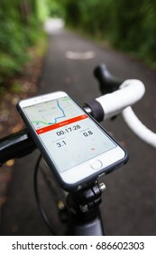BATH, UK - AUGUST 31, 2015 : Close-up of a smartphone mounted onto the handle bars of a road bike on a cycle path. The phone is displaying the Strava app, which shows navigation and pace information.