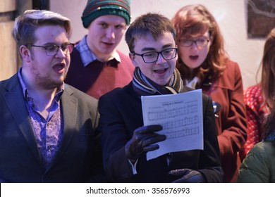 BATH, UK - DEC 9, 2015: A choir sings carols at the Christmas Market in the streets surrounding Bath Abbey. The market is held annually in the landmark Unesco World Heritage City.