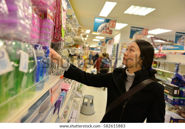 Bath, UK - December 8, 2014: A shopper browses a city centre Poundland discount store. The landmark Somerset city is home to many local and international retail stores and shops.