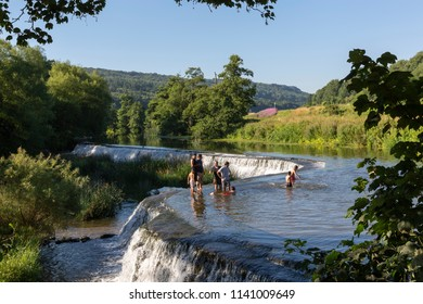 BATH, UK - JULY 15, 2018 : A group of men and boys taking a dip in the cool waters at Warleigh Weir, a popular river swimming spot near Claverton in Somerset during the 2018 heatwave.