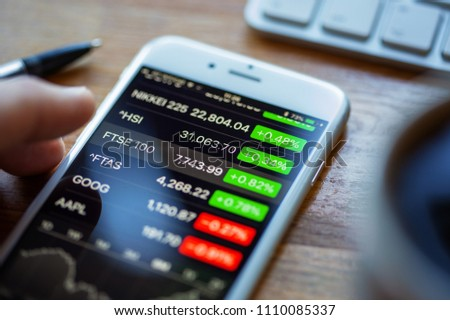 BATH, UK - JUNE 11, 2018 : An Apple iPhone 6 on a desk displaying stock market information using the Apple Stock app. A human hand hovers above the FTSE 100 index figure.
