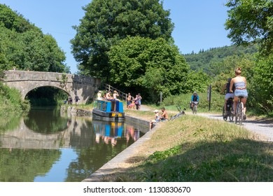 BATH, UK - JUNE 30, 2018 : People enjoying a sunny day on the Kennet and Avon Canal near Claverton in Somerset, England. Walkers, cyclists, boaters and anglers make the most of the summer heatwave.
