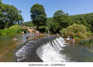 BATH, UK - JUNE 30, 2018 : People enjoying a hot day swimming at Warleigh Weir, a popular wild swimming spot near Claverton in Somerset. The summer heatwave of 2018 attracted hundreds of visitors.