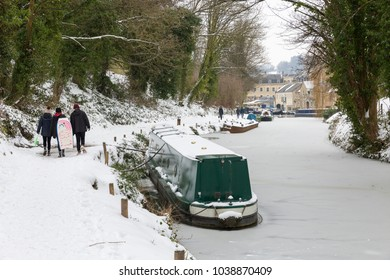 BATH, UK - MARCH 2, 2018 : People walking along the snow covered towpath on the frozen Kennet and Avon Canal near Bathwick Hill during the big freeze in early March 2018.