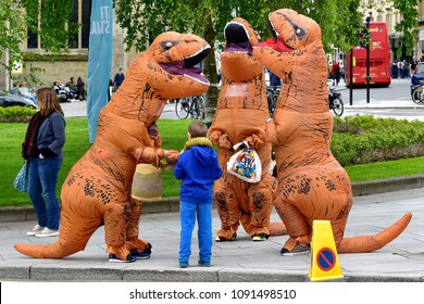 Bath, UK - May 12, 2018: People wearing tyrannosaurus costumes walk through the city centre.