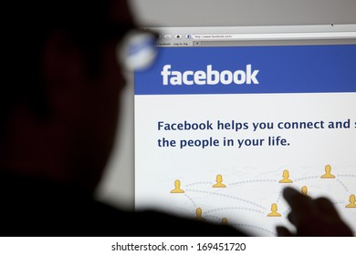 BATH, UK - MAY 4, 2011: Close-up of the Facebook homepage displayed on a LCD computer screen with silhouette of a man's head and hand out of focus in the foreground.