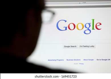BATH, UK - MAY 4, 2011: Close-up of the Google.com search homepage displayed on a LCD computer screen with silhouette of a man's head out of focus in the foreground.