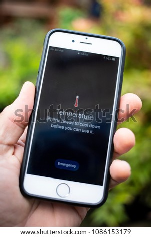 BATH, UK - MAY 8, 2018 : Close-up of a hand holding an iPhone 6 displaying  a temperature message warning that the phone is too hot to operate.