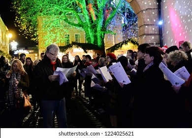 Bath, UK - November 30, 2014: People sing carols at the Christmas Market in the streets surrounding Bath Abbey. The popular market is held annually in the historic Unesco World Heritage city of Bath.