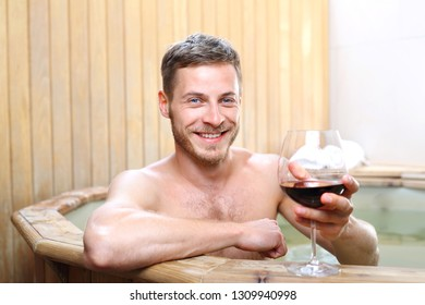 Bath in wine, a man relaxes in the spa with a glass of red wine.
