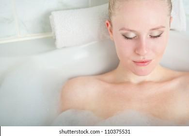 Bath woman enjoying bathub. Naturally beautiful female relaxing in bath with foam in bathroom