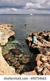 Bathers on a rocky cove on the island of Formentera, peace, calm, serenity, harmony, fullness, well-being, nature, natural, contemplate, meditate, breathe, grow, happiness, tranquility, fulfillment,