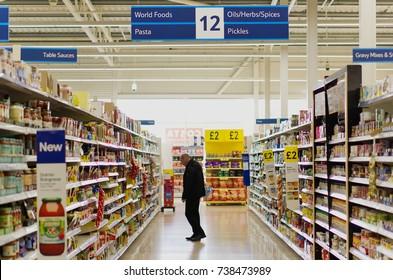 BATHGATE, SCOTLAND, UK - OCTOBER 11, 2017. A lone shopper in a Tesco supermarket aisle.