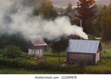 Bathhouse russian smoke in village at sunset