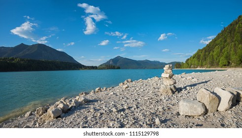 bathing beach lake walchensee with stack of boulders. beautiful and clear cold mountain lake bavaria.
