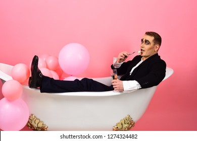 Bathing and relaxing. Mime actor enjoy bathing in bath tub. Mime man has celebration party with food and drink. Comedian actor celebrate holidays. Happy bubble bath day. Creating a spa atmosphere.
