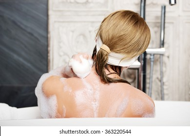 Bathing woman cleaning her back with soap.