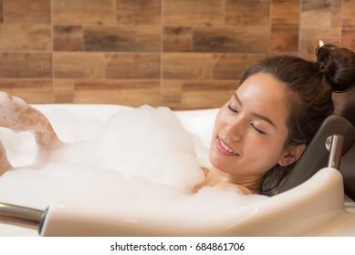 Bathing woman relaxing in bath smiling relaxing. Multicultural Asian / Caucasian young woman in bathtub.