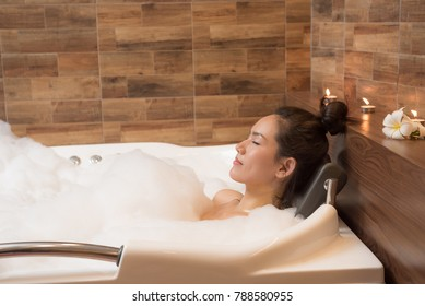 Bathing woman relaxing in bath smiling relaxing. Multicultural Asian / Caucasian young woman in bathtub.