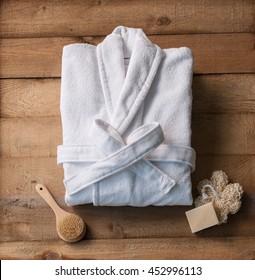 bathrobe bath soap and loofah brush behind wooden table