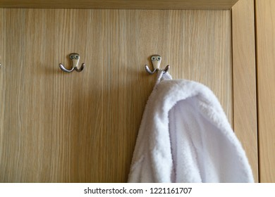Bathrobe hanging on the hook. Classic bathrobe hanging on wooden abstract wall hook mounted against wooden wall
