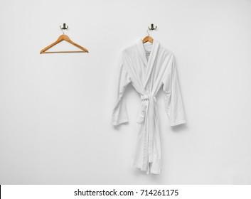 Bathrobe hanging on white wall