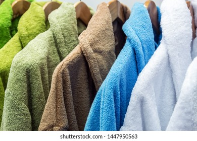 bathrobes of different colors hang on a hanger in the store