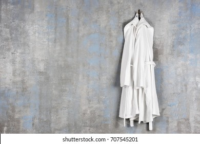 Bathrobes hanging on grey wall
