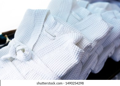 bathrobes. several white waffle bathrobes neatly folded for spa visitors . close up