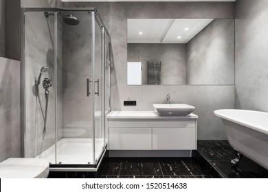 Bad mit Waschbecken, Duschkabine, großem Spiegel und verchromtem Silberheizgerät oder Handtuchkühler an grauer Wand. Loft Stil in neuen Wohnung. Modernes Haus mit zeitgenössischem Interieur