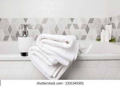 Bathroom, body care products and towel . Bath preparation. White interior of bathroom. Shampoo, shower gel and other bathing accessories. Toothbrush and soap dispenser. details of bathroom