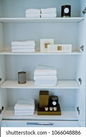A bathroom cabinet with racks with well organized    accessories :  towels, pieces of soap, aroma candles and so on.