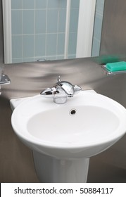 bathroom ceramic sink in stainless steel interior. taps and soap in modern restroom